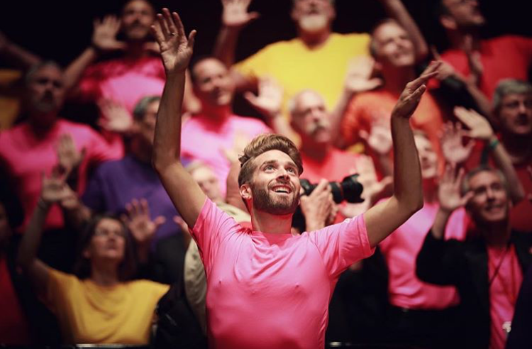 Choir performing with hands raised in colourful t-shirts