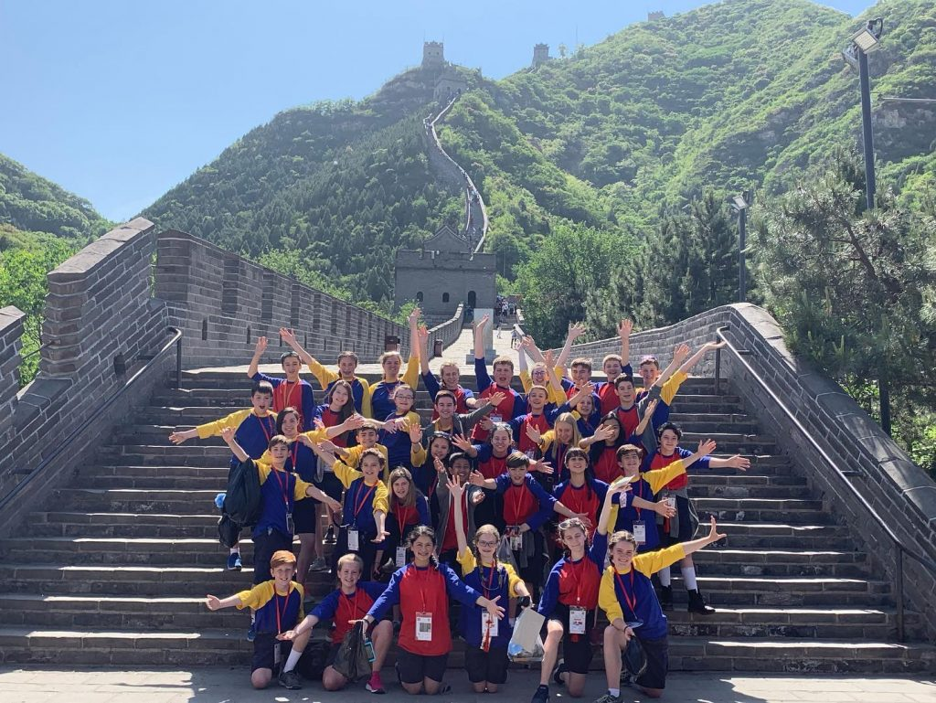 Group post on great wall of china steps, arms extended