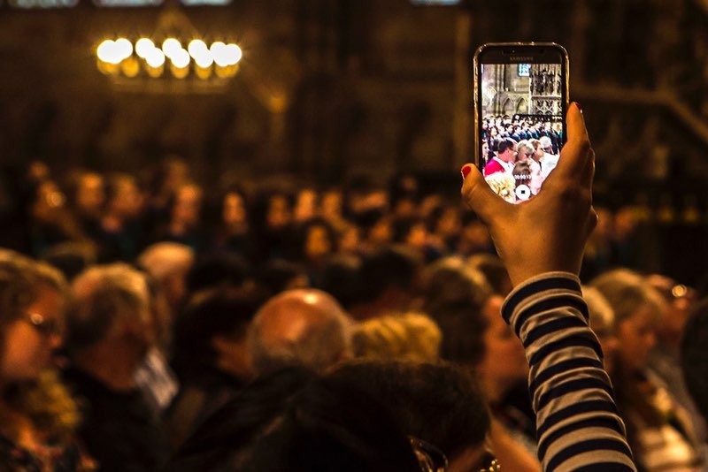 An audience member filming a concert through their smartphone