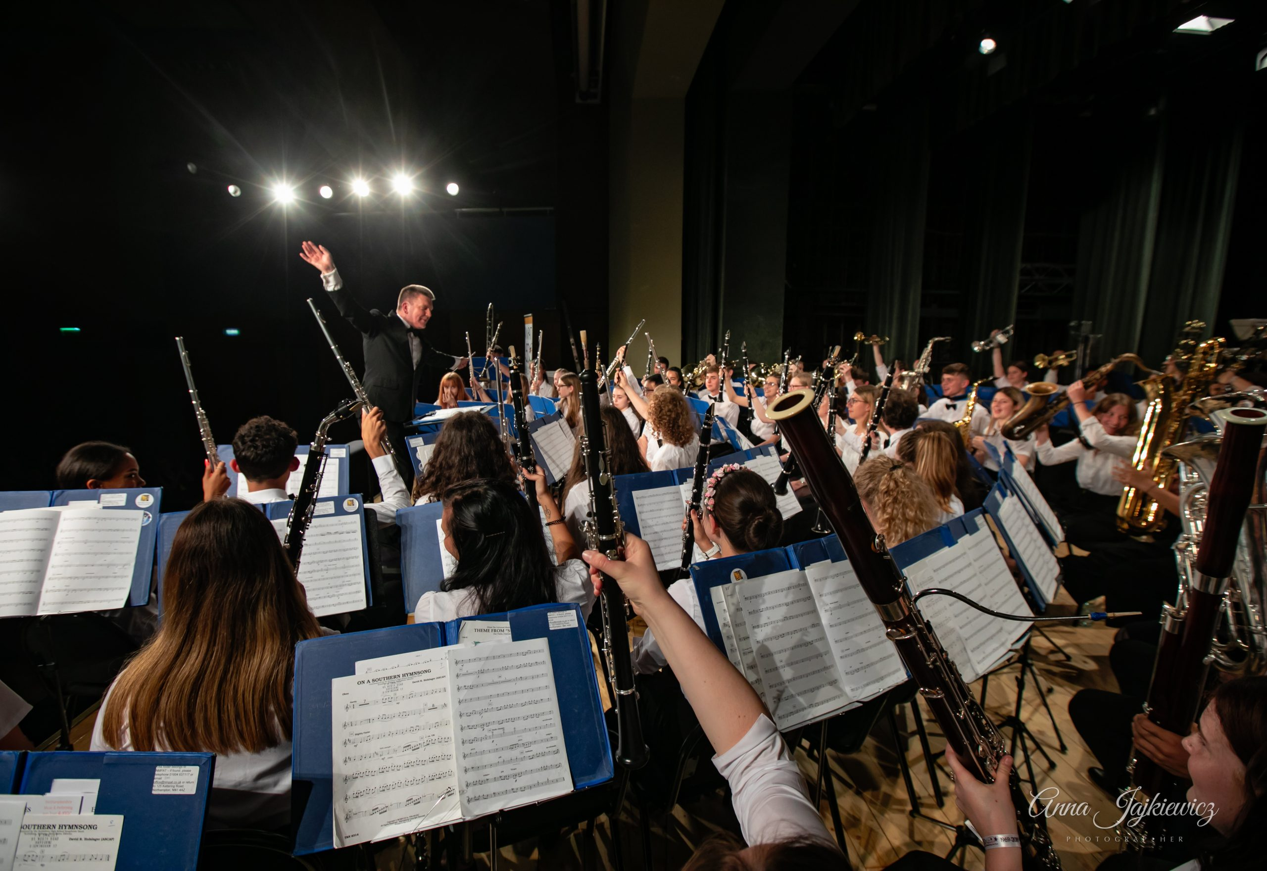 Orchestra performing on tour, instruments raised