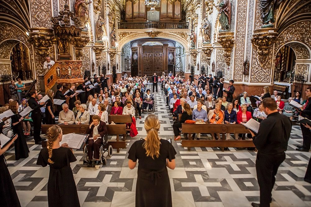 Choir performing to full audience in ornate church
