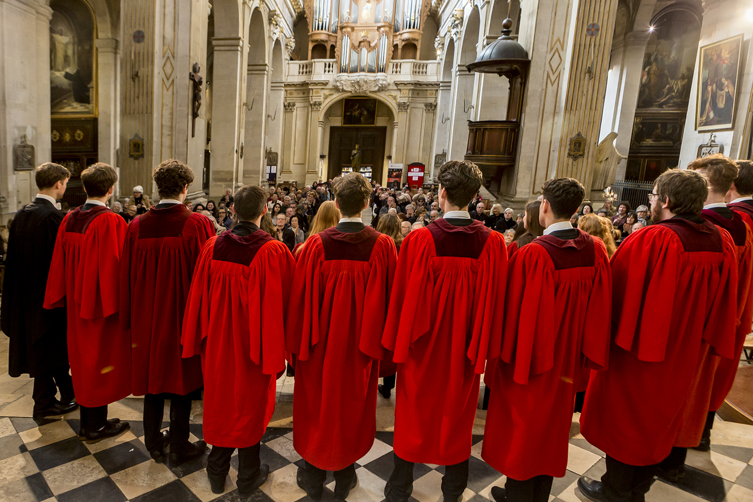 Choir in red cassocks performing to full church