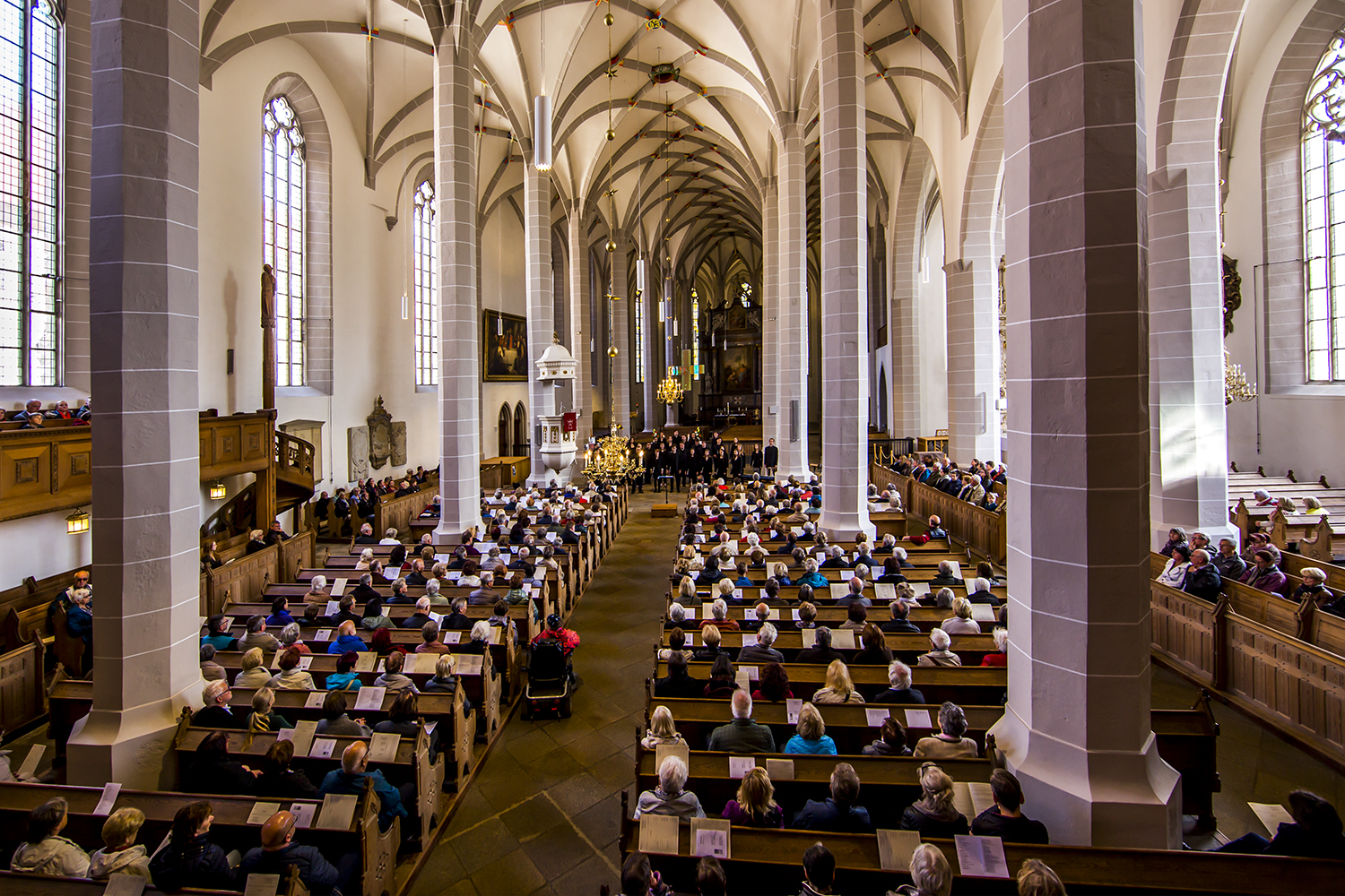 Choir performing to a full audience in a huge cathedral