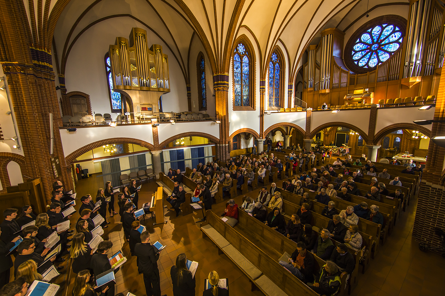 Panoramic photo of choir performing to an audience in a church