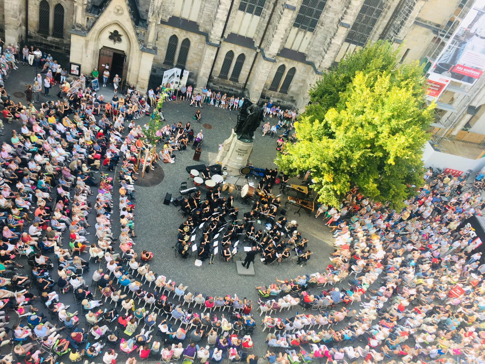 Orchestra perform to thousands of audience members, aerial view