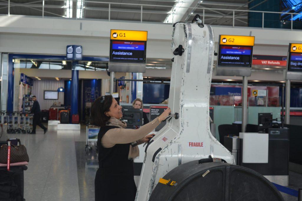 Staff member assisting the check in of a large double bass