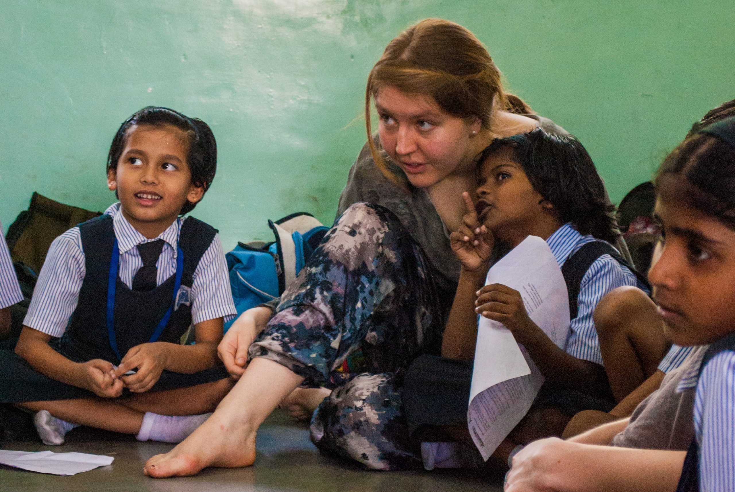 Tour member sitting and working with local students from India