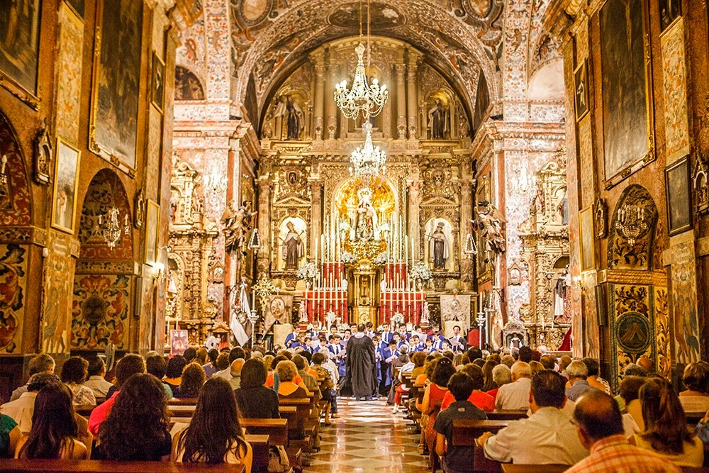 Choir performing infront of ornate spanish altar