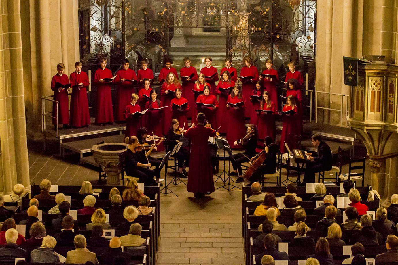 Choir in red cassocks performing with string ensemble to full church